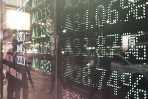 Stock exchange market display screen board on the street showing stock rises in green color.