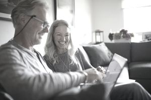 older couple sitting on a couch looking at a laptop