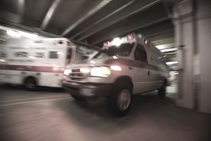 Ambulance with lights on in parking structure