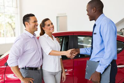 Couple shaking hands with a car salesperson after buying a car