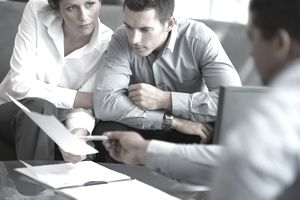 Man and woman holding paper work and consulting with another man in an office.