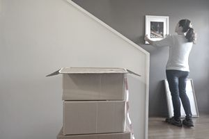 Woman standing with moving boxes, hanging a picture on the wall of the home she just bought