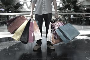 Man holding several shopping bags in mall after a spending spree.