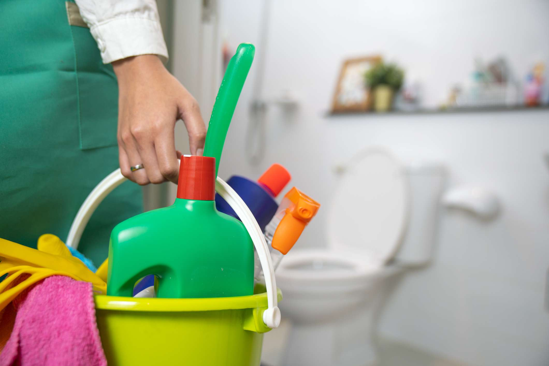 The cleaning woman is standing in the bathroom holding a blue bucket full of chemicals and facilities for storing her hands.
