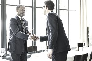 Two people in business attire shake hands in an office setting.