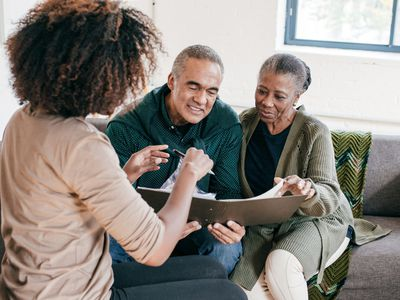 Woman helping older couple with documents