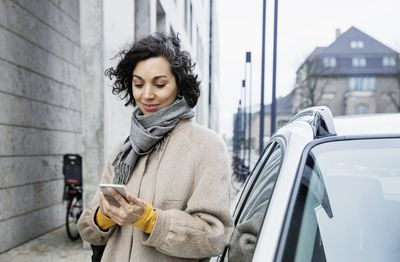 Person on their phone next to a car