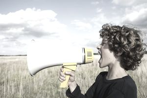 a boy yelling into a megaphone standing in a field.