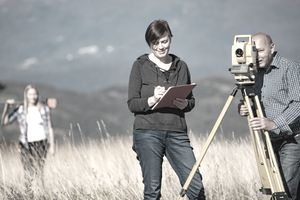 Surveyors Measuring Land in Rural Scene