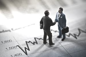 Two businessmen figures shaking hands on a stock market graph