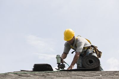 A construction worker in a protective helmet fixes a roof.