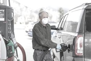 Man wearing surgical gloves and mask refueling car at gas station