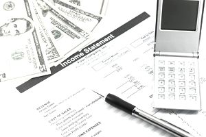 An income statement showing the top-line revenue laying on a desk with cash and a cell phone.