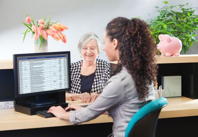 Customer at Retail Banking Counter Window with Bank Teller