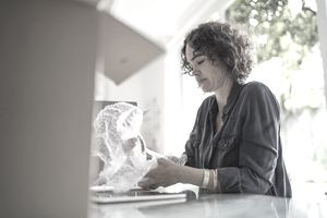Woman wrapping fragile object as she is packing to move