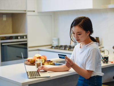 person sitting at kitchen counter looking at debit card while on computer