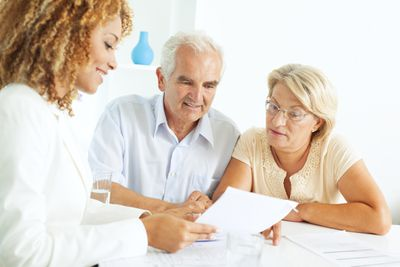 elderly couple looking over estate planning documents with an attorney