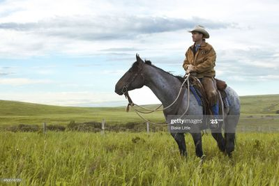 Man sitting on horseback looking out over green, rolling hills