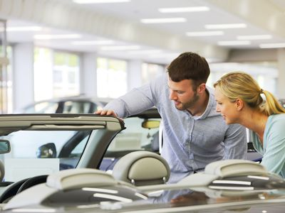 Couple looking at a convertible in a dealer showroom