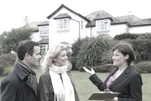 real estate agent showing house to couple