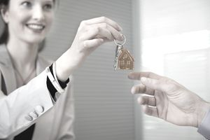 woman handing keys to new home to another person