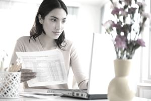 Woman holds a billing statement in one hand and looks at laptop