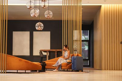 A smiling woman sits on a couch in a spacious and luxurious hotel lobby and speaks on the phone.