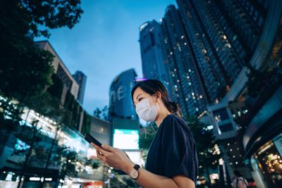 Young Asian woman with protective face mask using smartphone on the go, against illuminated neon commercial signs in city street in downtown district at night. The new normal of everyday life. Business on the go