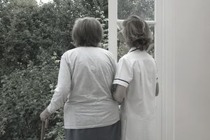 A nurse supporting an elderly woman as she stands at an open door