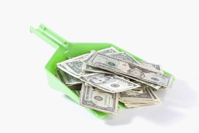 a dustpan filled with money