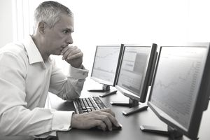 Man monitoring stock trades on computers