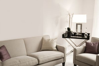Showing a sofa, chair, table, lamp, and blank walls as the essentials of what is needed to decorate your first apartment