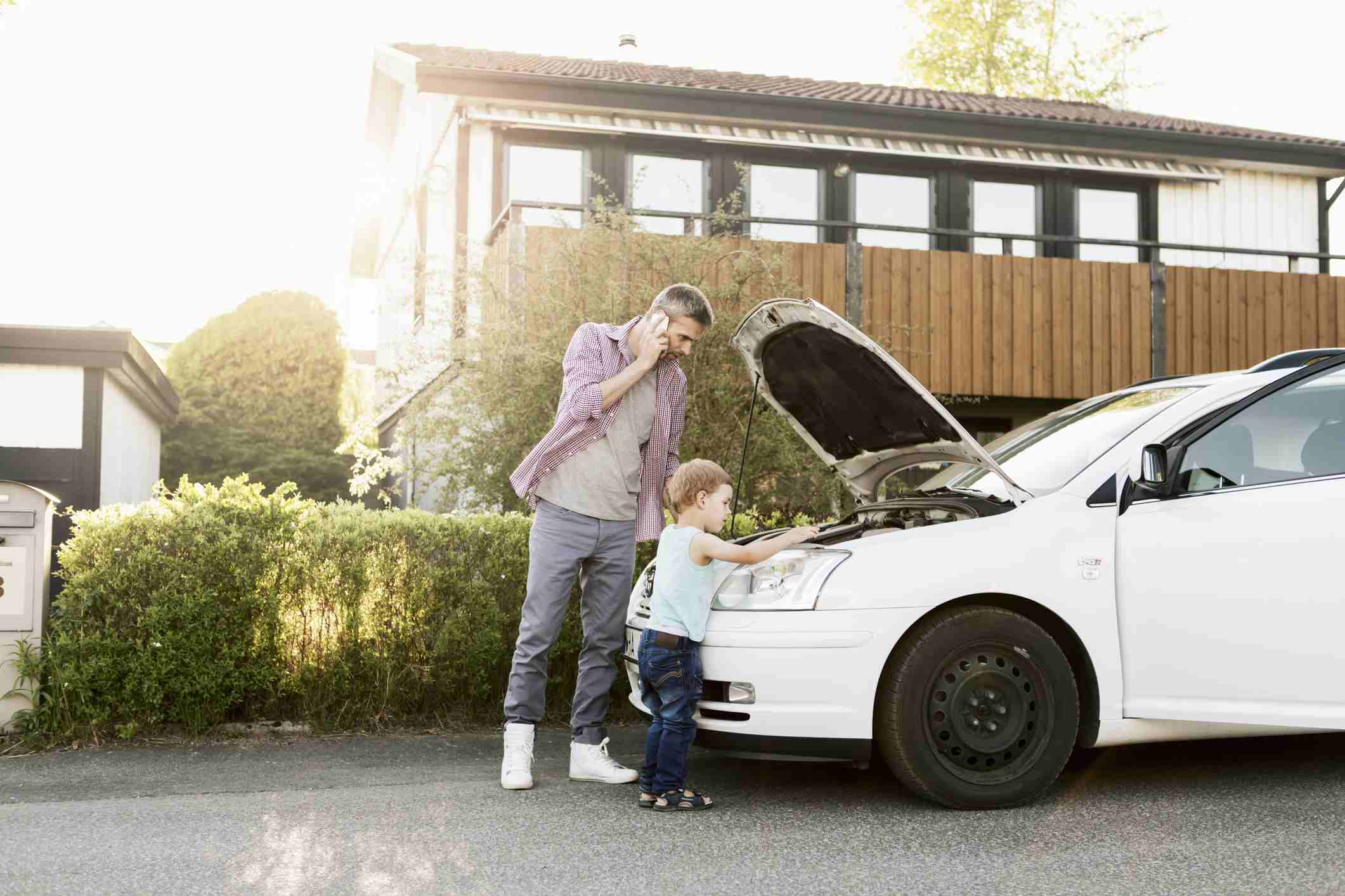man and young son near a car with an open hood