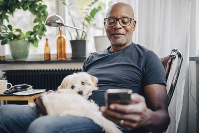 Smiling retired senior male using smart phone while sitting with dog in room at home.