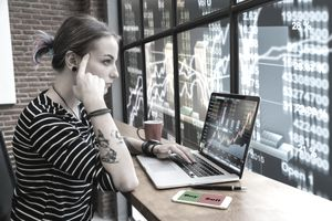a young woman looking at a laptop with stock chart in the background