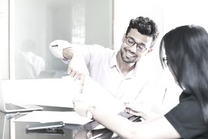 Man showing investment charts to a woman in an office