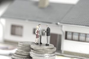 Figurines on a stack of coins, miniature house in background