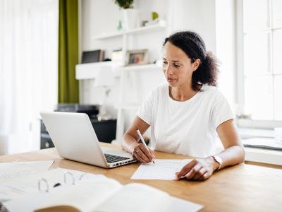 Mom Sitting At Kitchen Table Working From Home