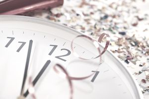 a clock next to confetti, a noisemaker, and ribbon