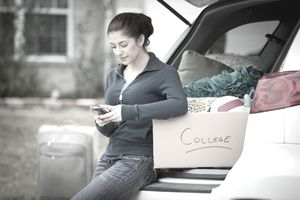 Woman packing for college rests by her car