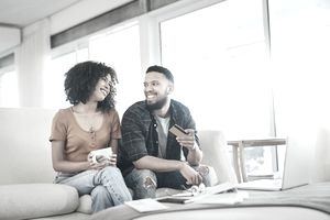 A smiling couple debates whether to get their tax refund on a prepaid card as they sit in their bright living room.