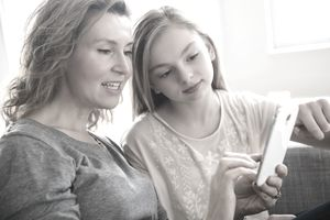 Caucasian mother and daughter using cell phone in living room
