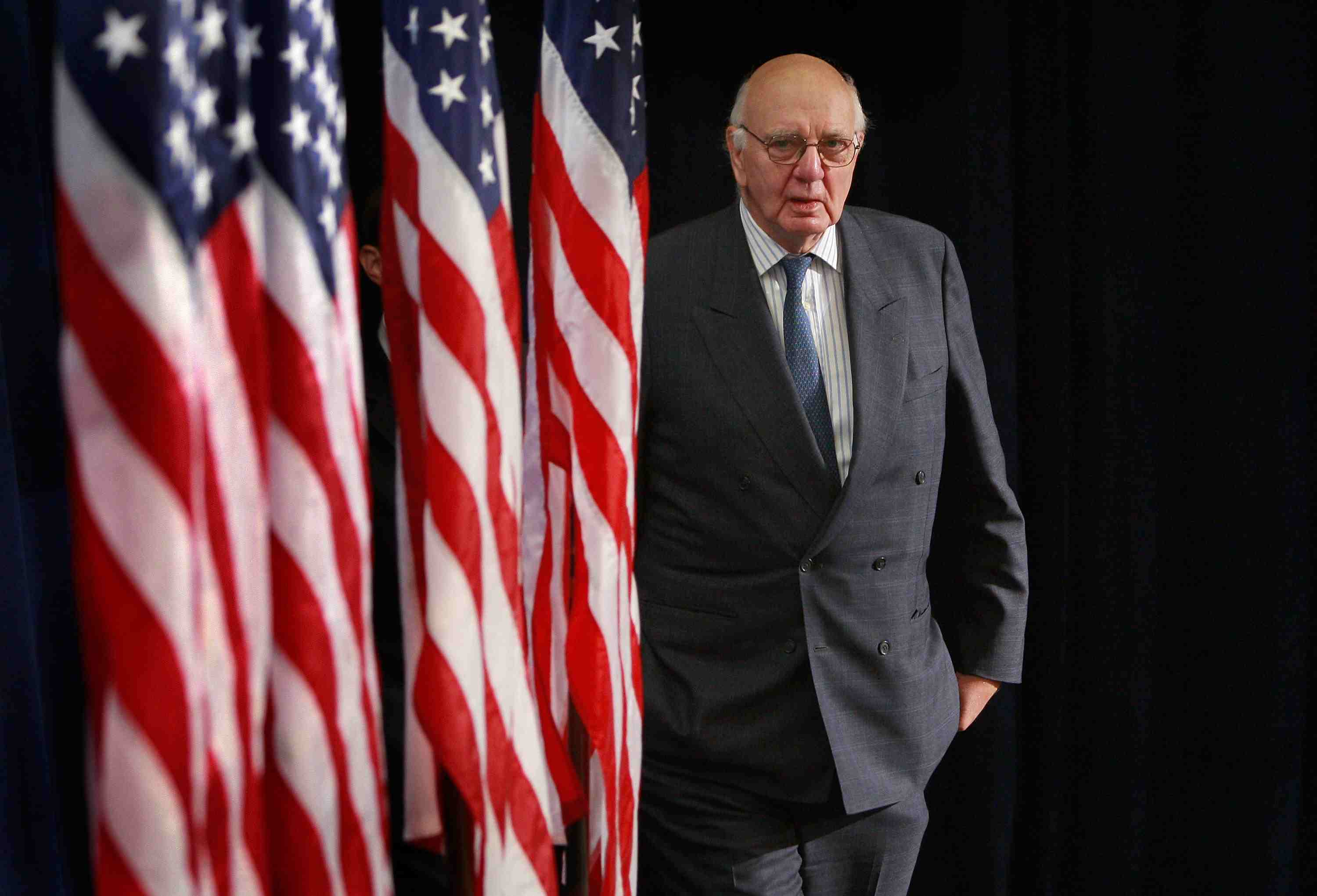 Federal Reserve Chairman Paul Volcker standing next to four US flags as he ended stagflation
