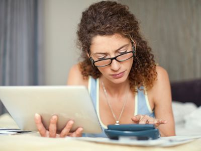 Young woman with calculator and digital tablet
