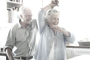 Happy senior couple dancing together at home
