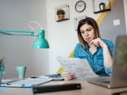 Woman with a quizzical expression examining financial documents