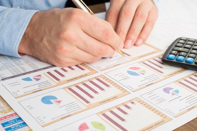 Close-up of man's hands working on KPI calculations for a business