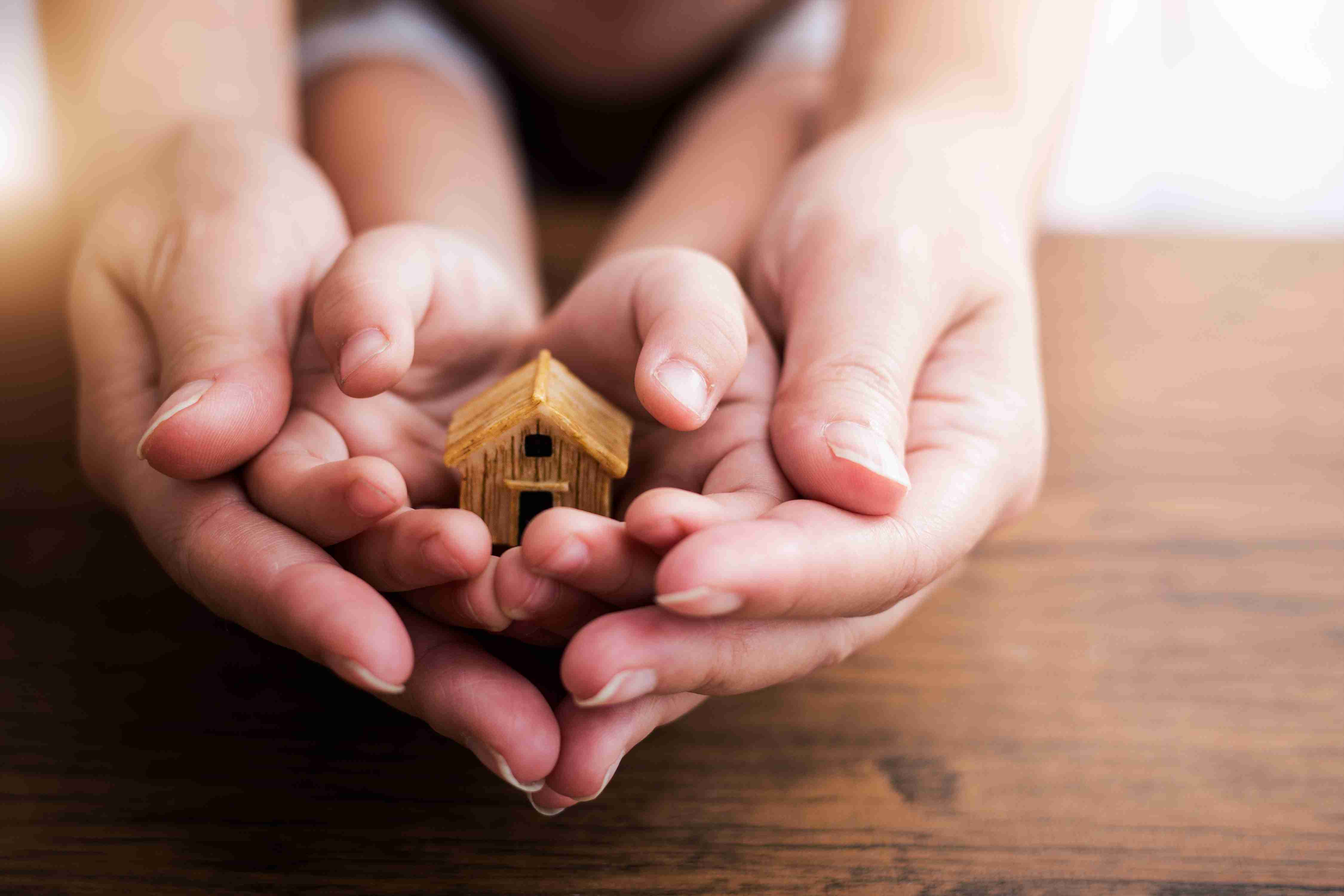 Hands holding small house shows that people set budgets to reach a future goal