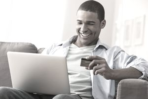 A man using his credit card online with his laptop