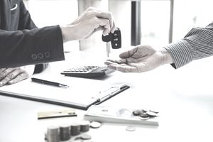 Midsection Of Businessman Giving Car Key To Customer On Desk